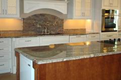 Crema Bordeaux granite countertops and island with full height splash behind sink.