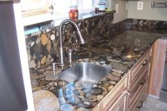 Gold Marinace countertop with full height splash behind sink