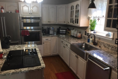 Granite kitchen countertops with cooktop in island and farm sink in Prince Frederick, MD