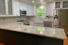 African Rainbow Granite countertops with a porcelain apron front farm sink in Prince Frederick, MD