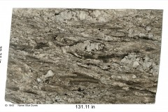 Blue Dunes granite 1643.  Heavy in movement with rich browns and golds and accents of blue. Would go well with a white, gray or neutral color scheme.  Mid price range.